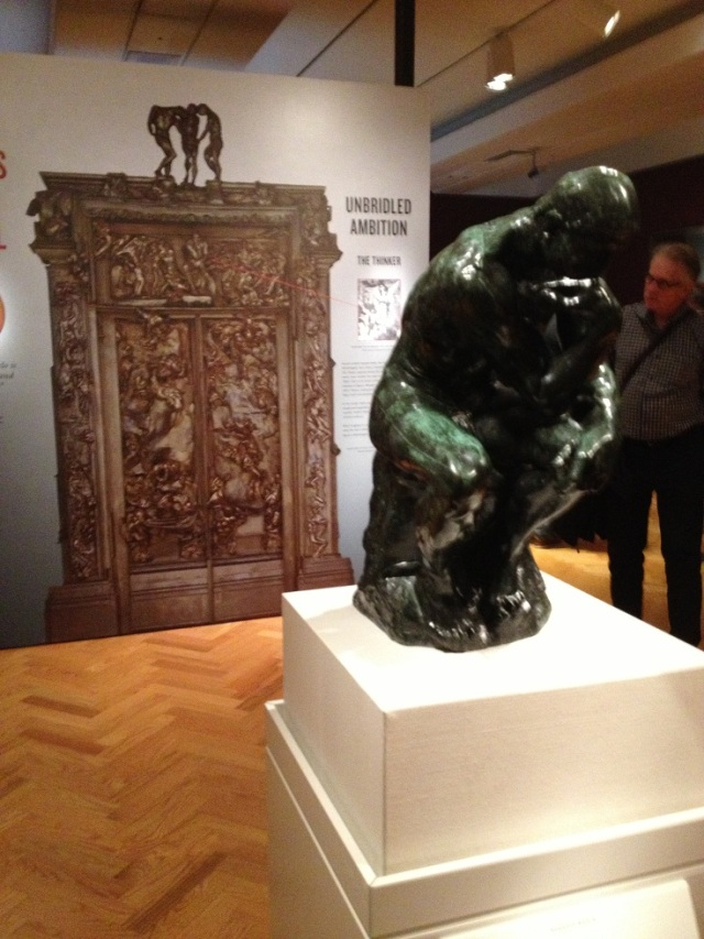 Auguste Rodin French, 1840-1917 Le Penseur (The Thinker) conceived 1880; cast early 1920s bronze Height: 69.9 cm Gift of Mrs. O.D. Vaughan, 1977, shown in front of an image of Rodin's Gates of Hell.  At first glance i thought this was Michaelangelo, not Rodin.